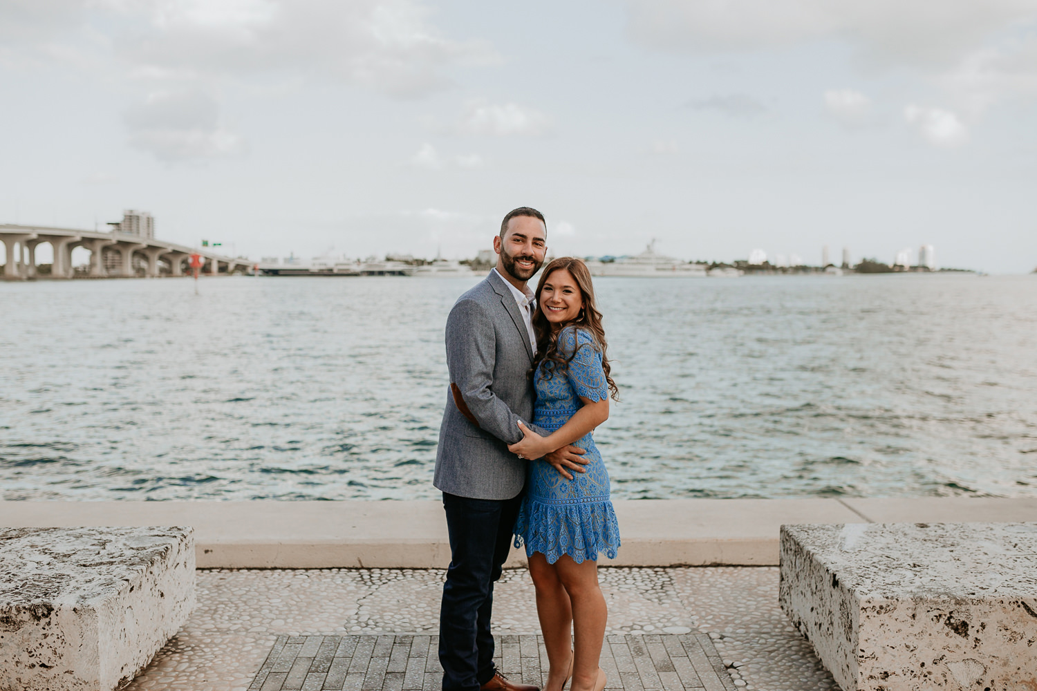 newly engaged couple smiling at the camera with Miami water in the background
