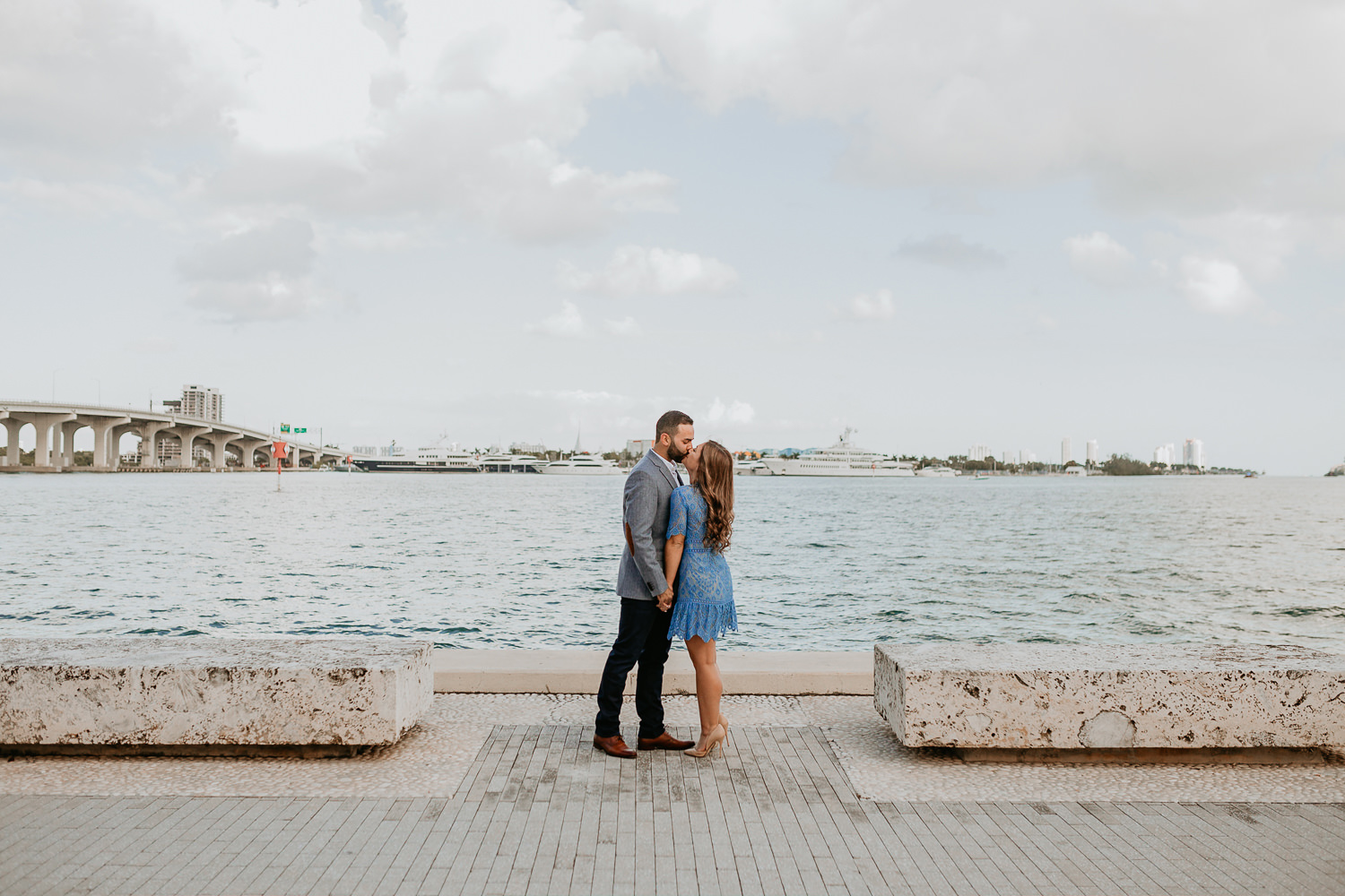 couple facing each other kissing Miami water in the background