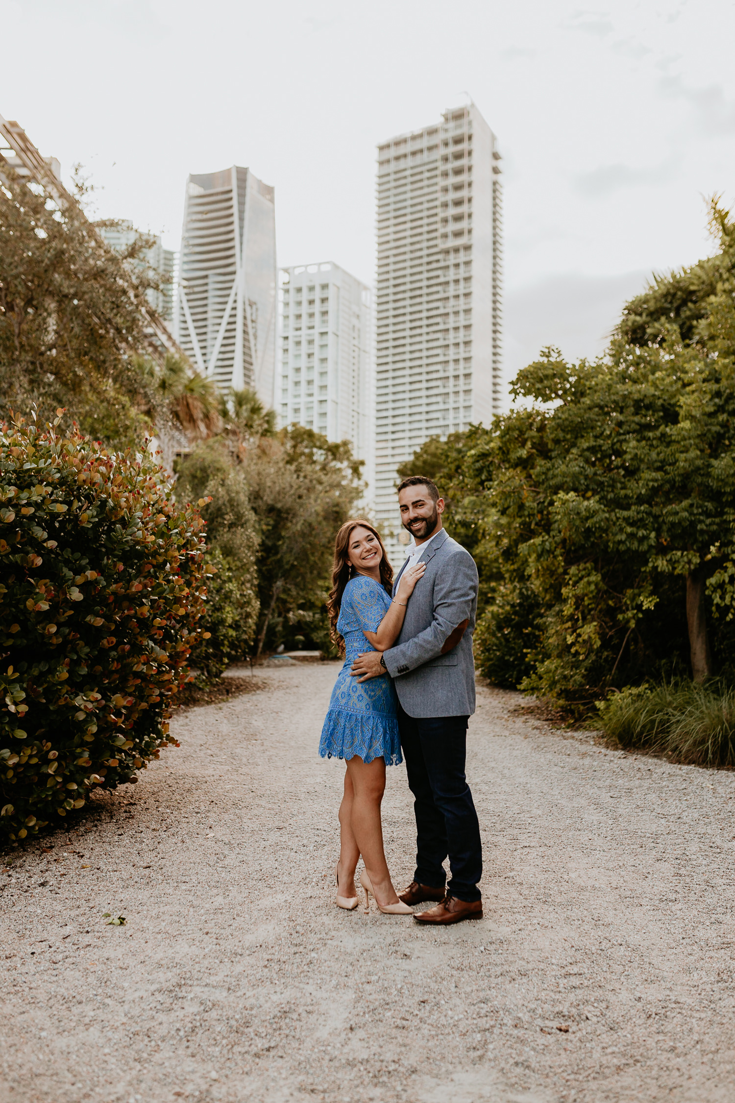 newly engaged couple posing for camera between rows of trees in downtown Miami