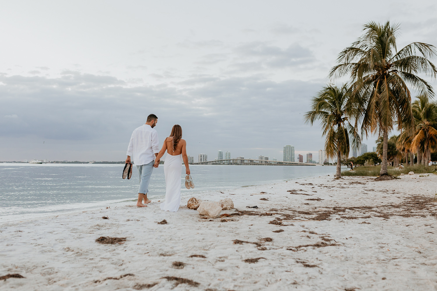 engaged couple wearing white loose clothing walking on the sands