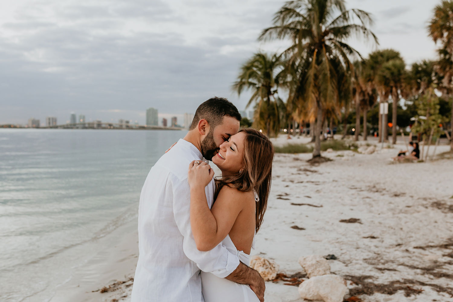 couple holding each other tightly on Hobie island beach with Miami in background