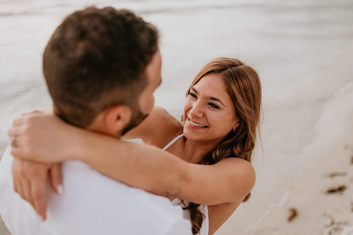 close up of girl with her arms around her fiancé at the beach