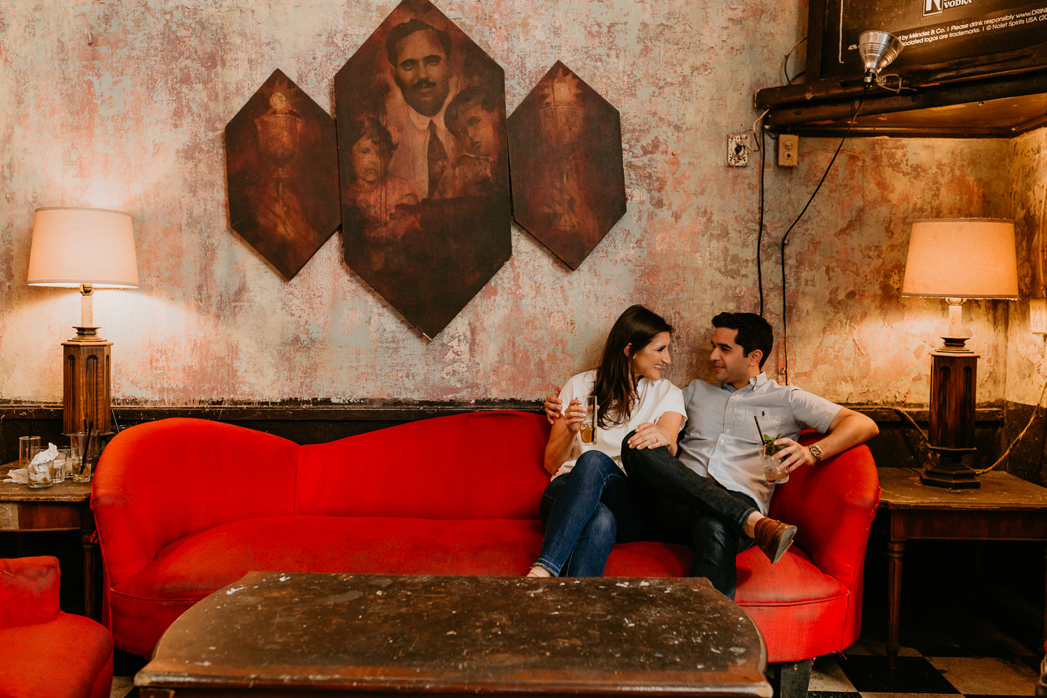 couple sitting together on the edge of a red holding cocktails at La Factoria