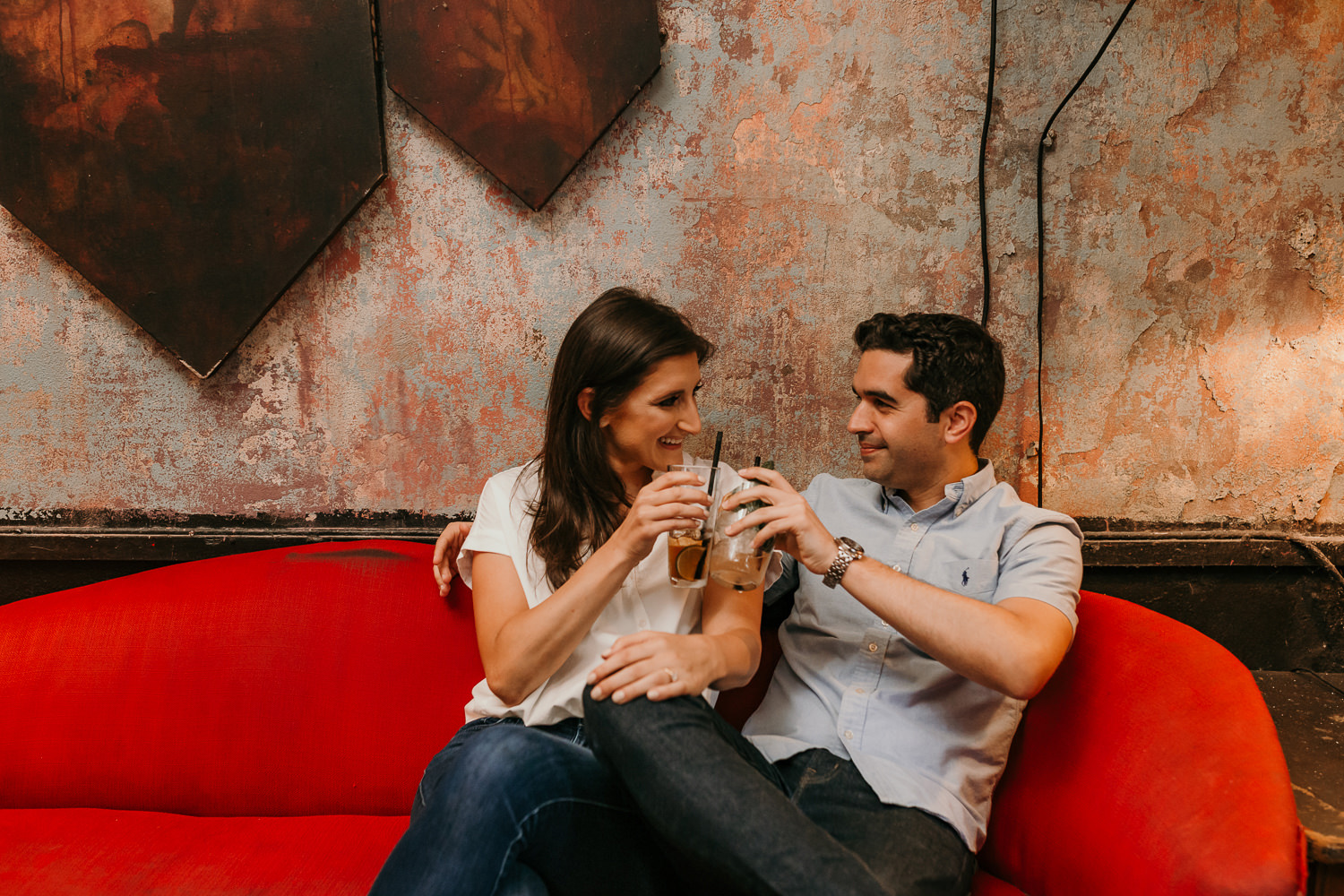 closeup of couple sitting together toasting and smiling at each other on red couch