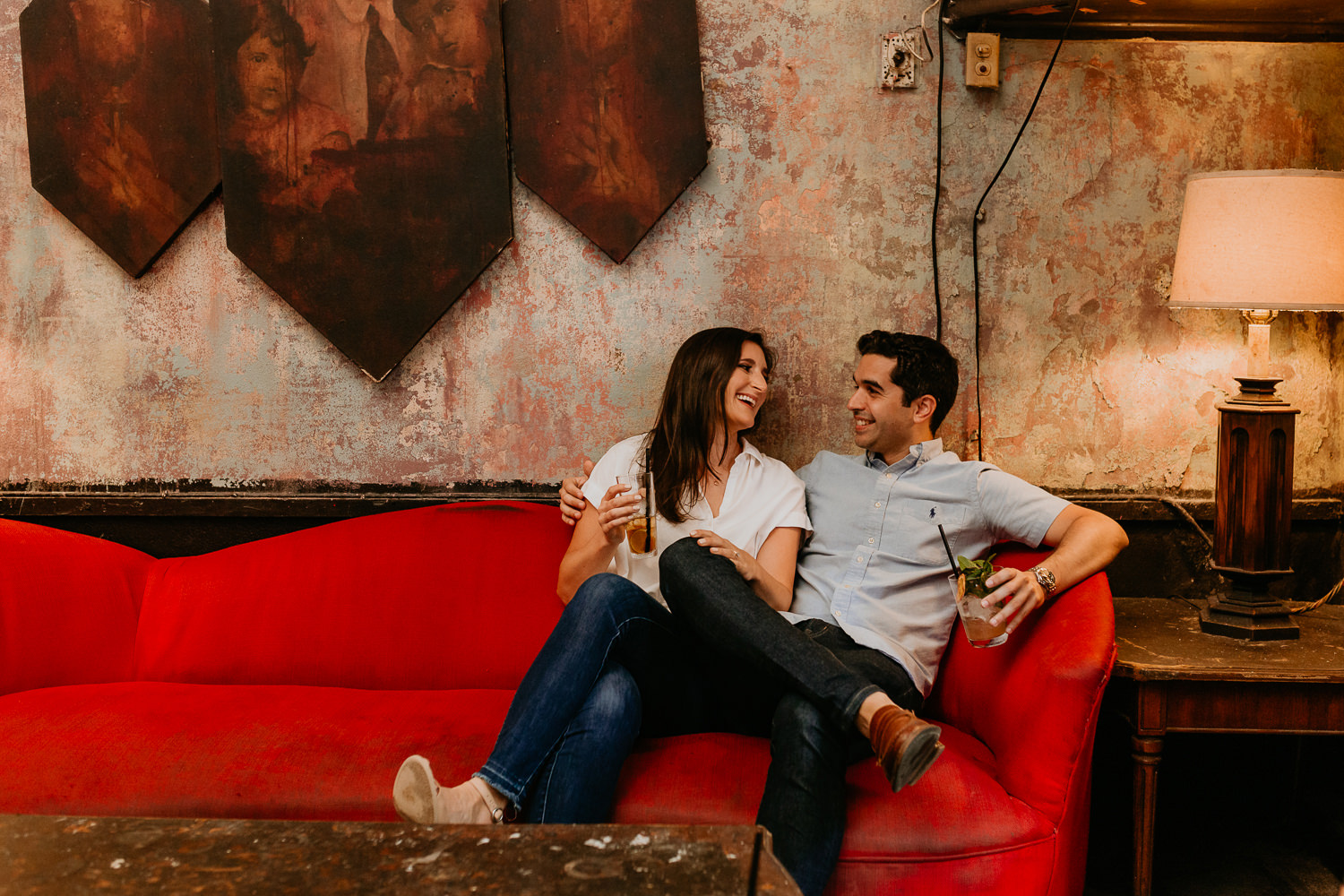wide of couple laughing at each other on red couch at La Factoria cocktail bar