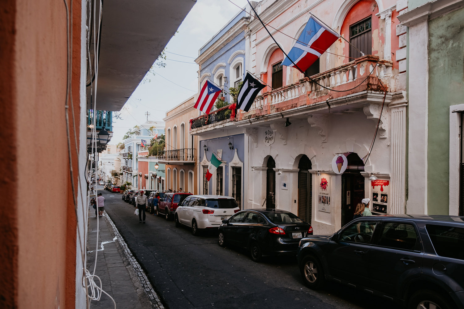 old San Juan street with many flags looking out from la factoria's window