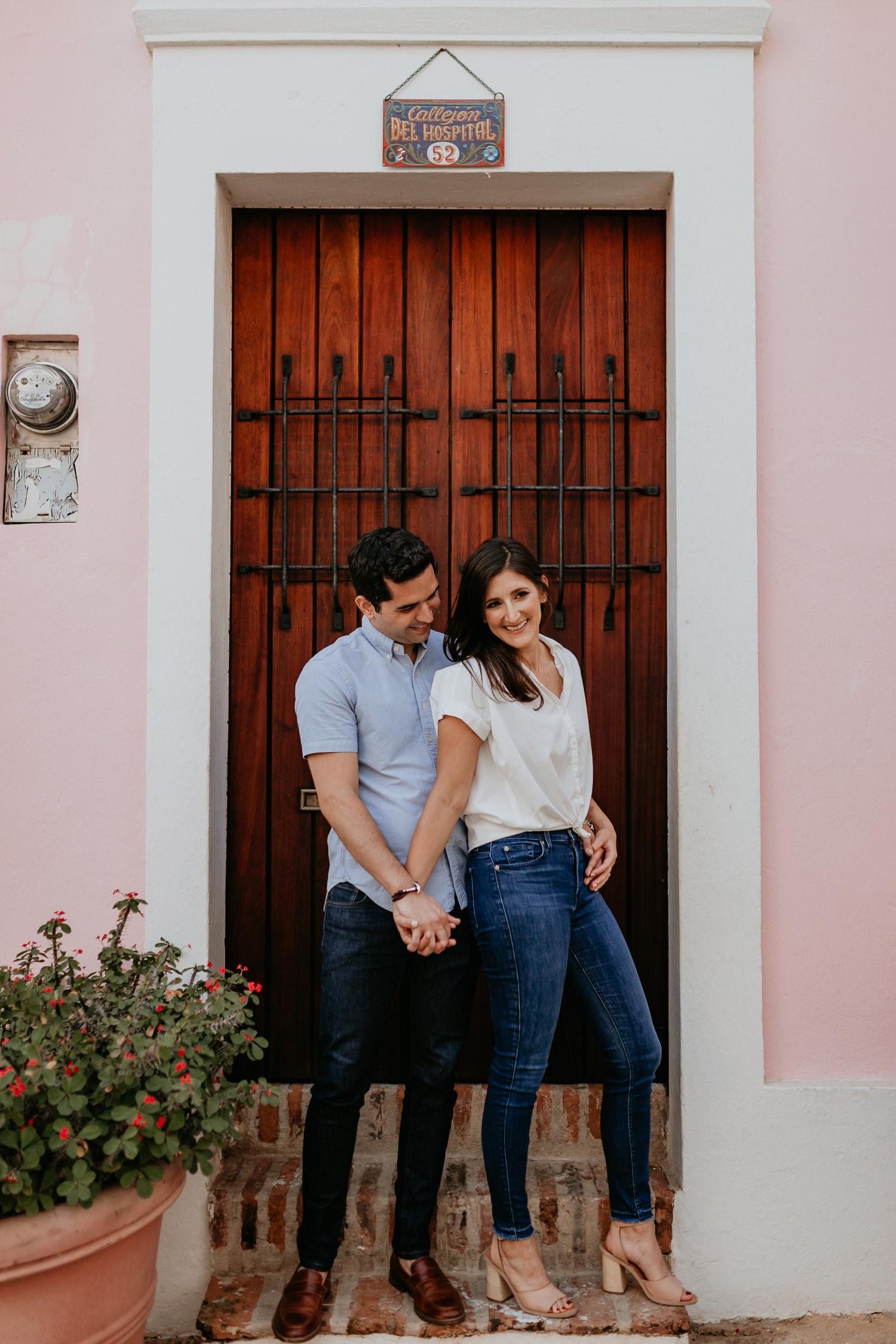 close up of couple standing together in front of wooden door holding hands smiling
