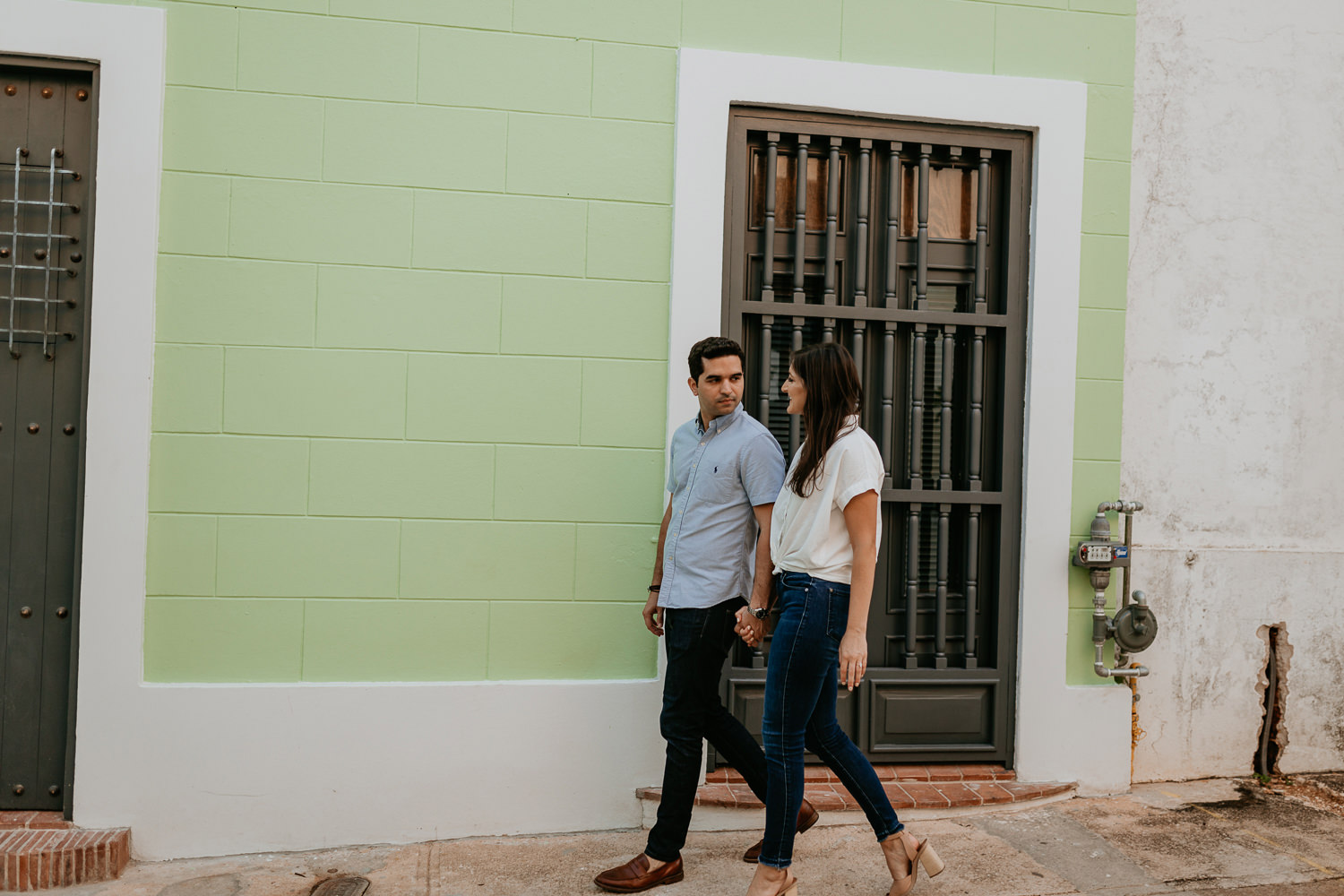 couple walking holding hands passing a lime green San Juan house