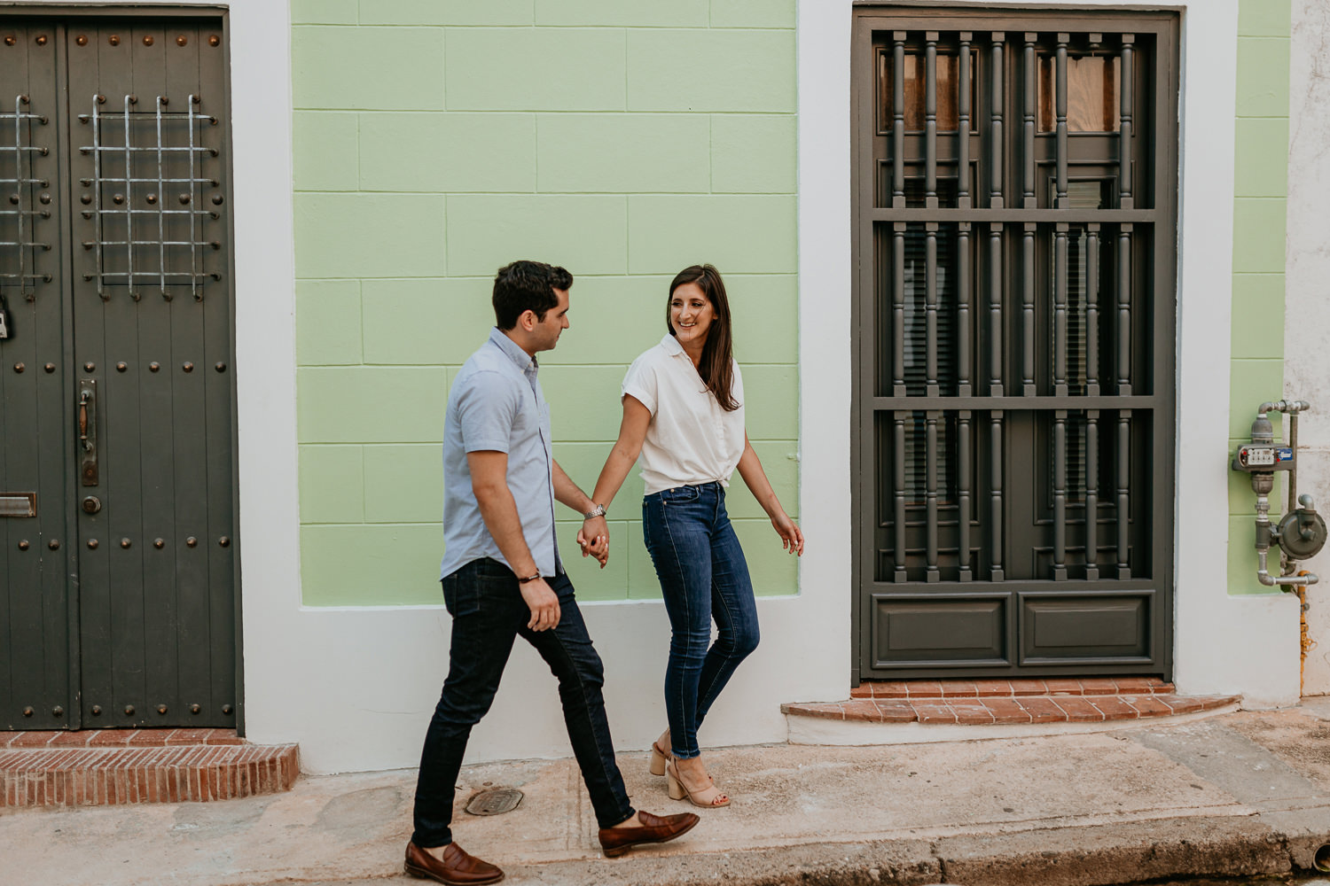 couple walking holding hands and laughing as they pass a lime green wall