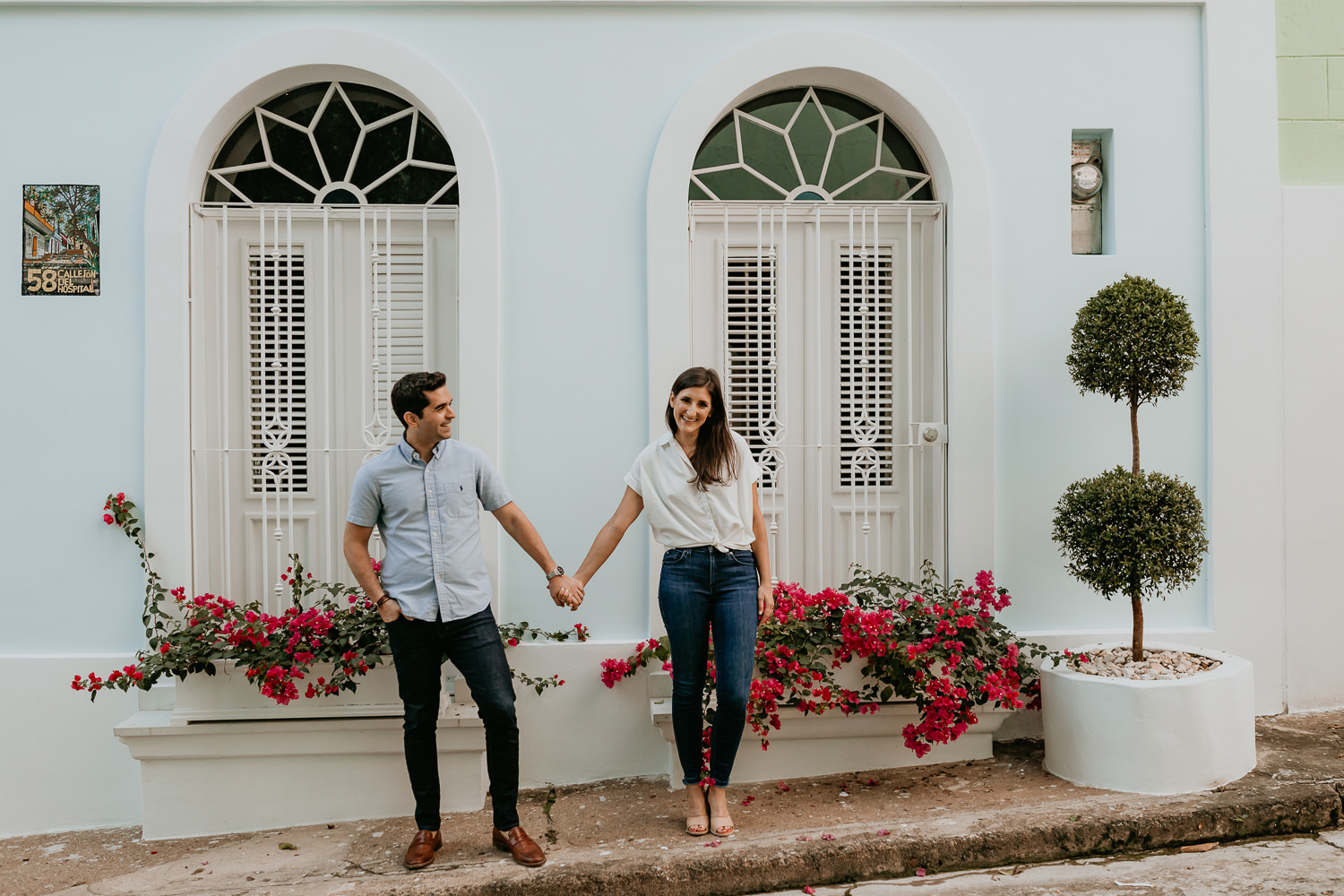 couple standing side by side holding hands in front of sky blue house with red flowers