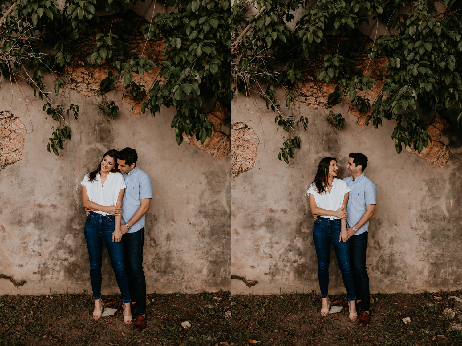 couple being intimate in front of stone wall with green leaves above them