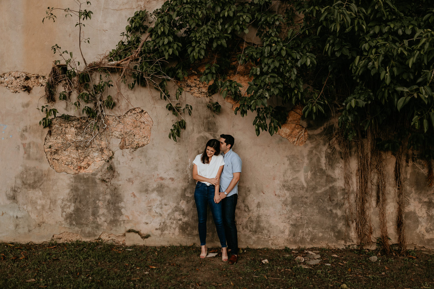 man kissing woman on forehead in front of stone wall with green leaves above them