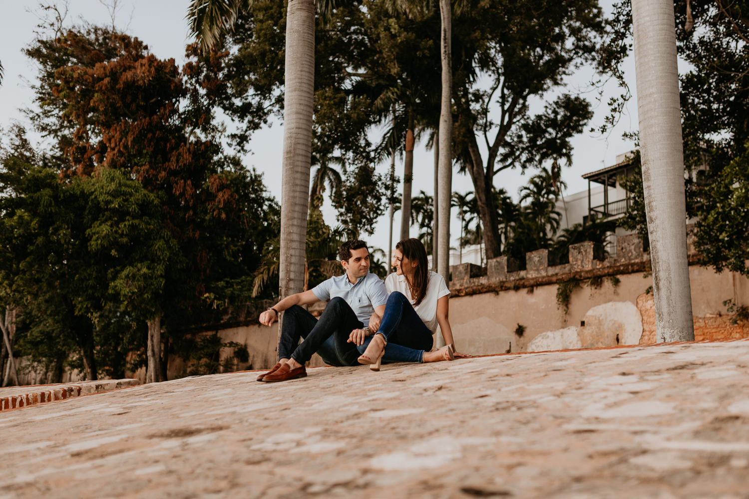couple sitting on el Morro stone wall arms around each other