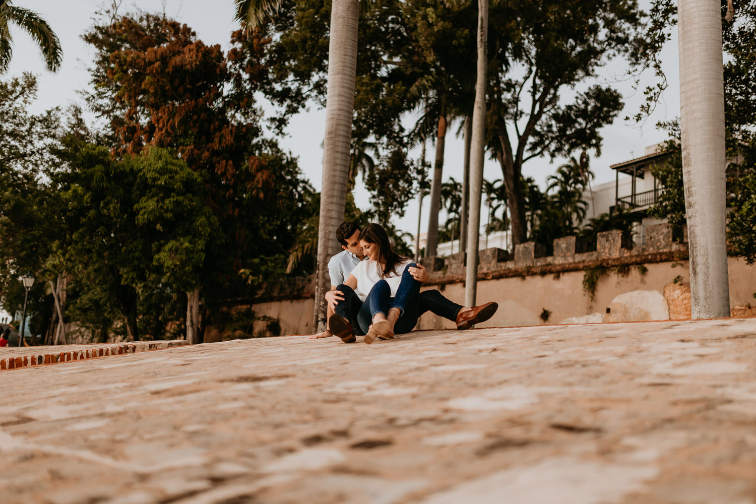 woman intimately sitting between man's legs both sitting on stone wall