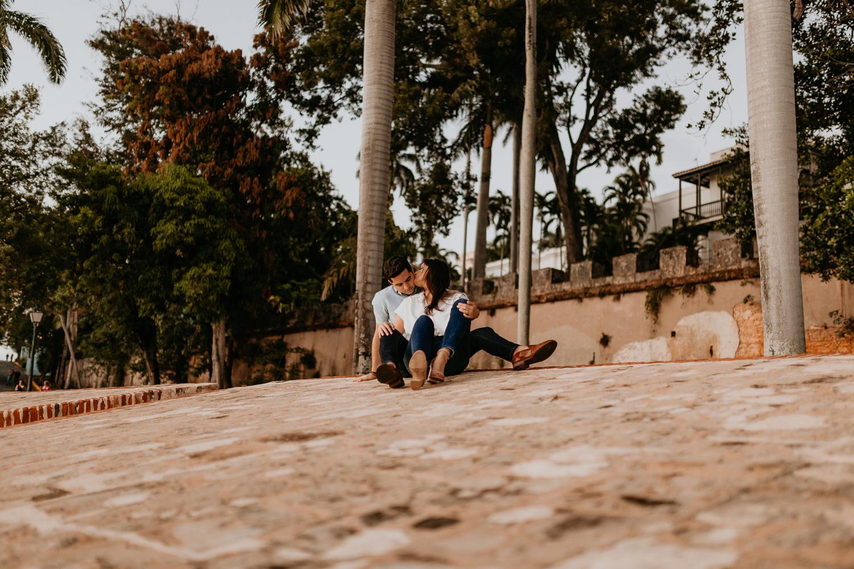 woman sitting between man's legs both sitting on stone wall, she's kissing his cheek