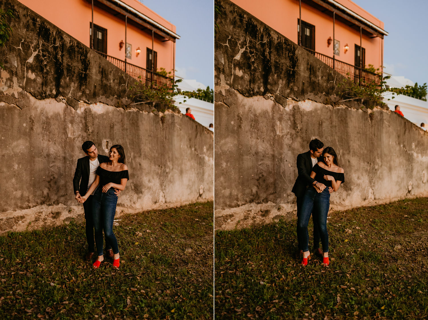 couple holding each other in front of stone wall during sunset lighting