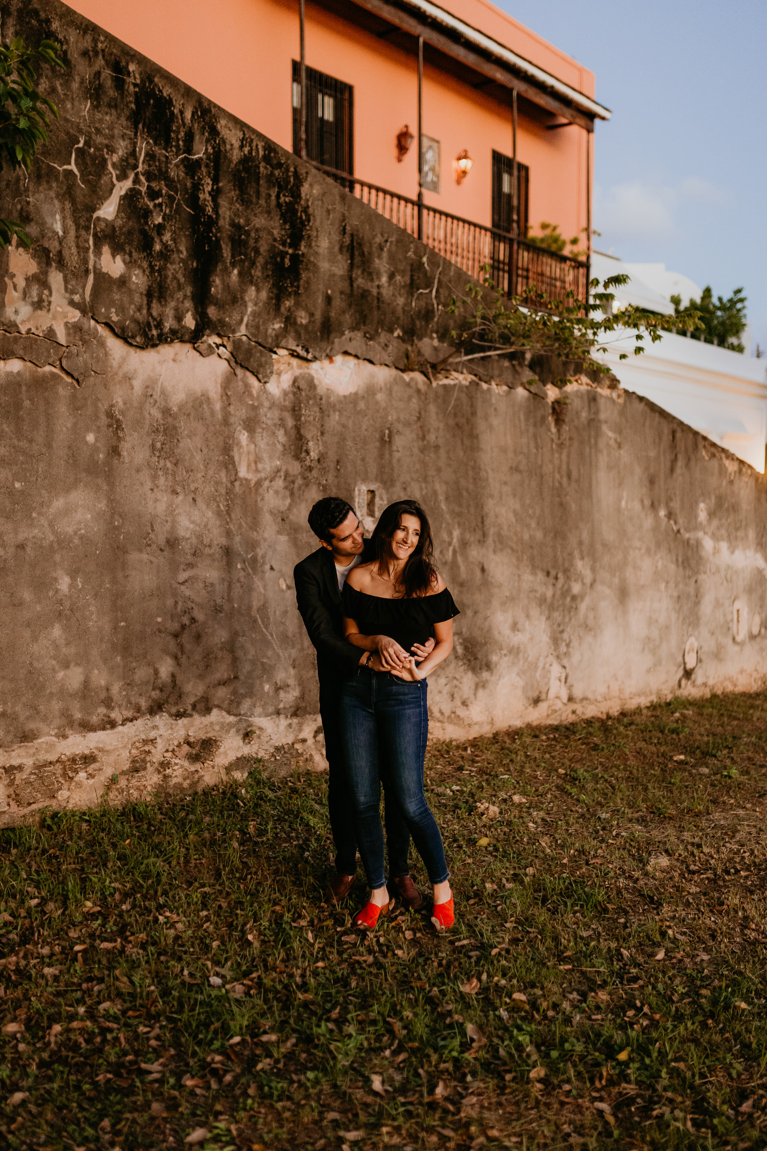 man hugging woman from behind, her smiling hard, in front of stone wall sunset