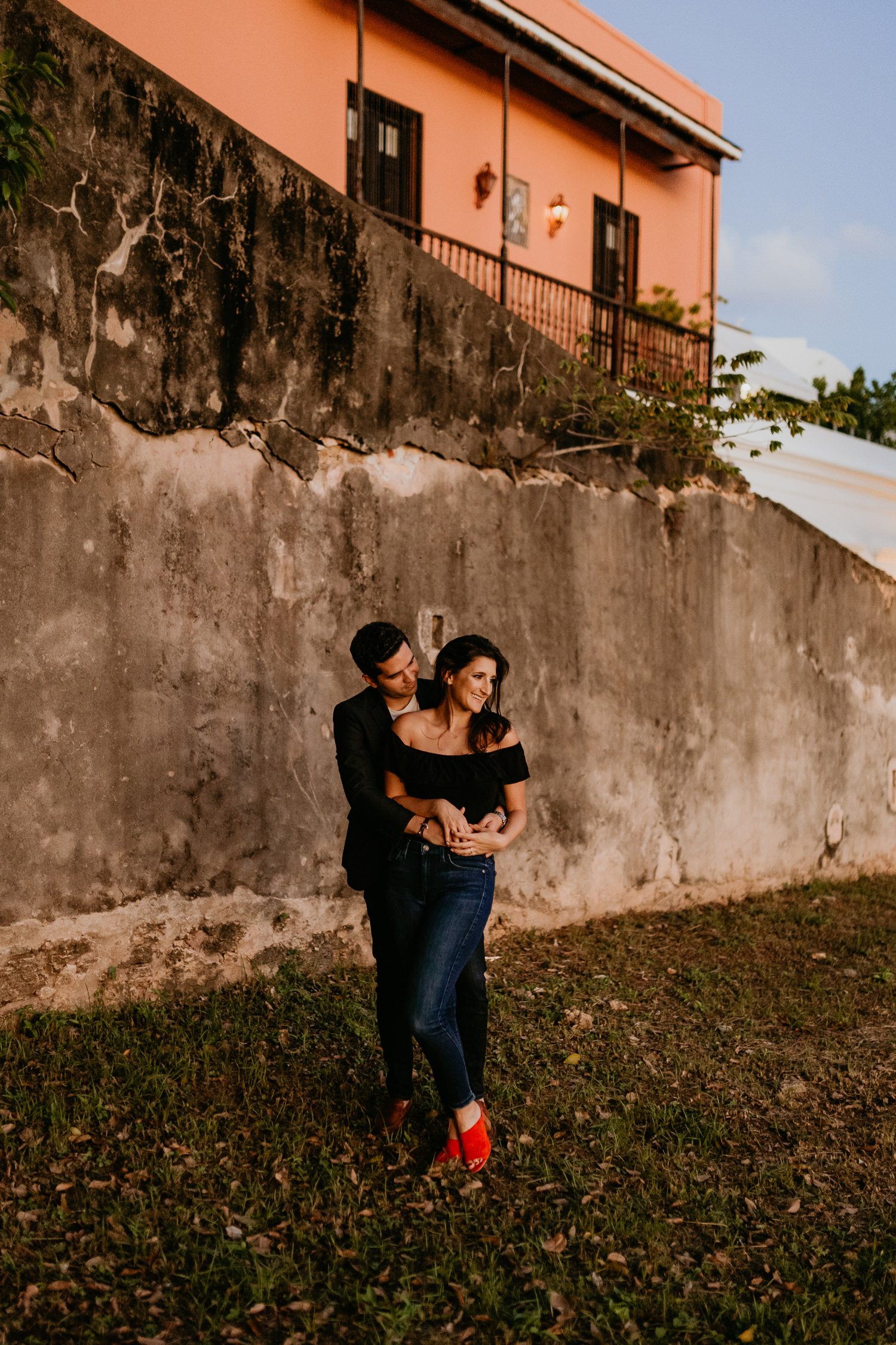 man hugging woman from behind in front of stone wall during sunset