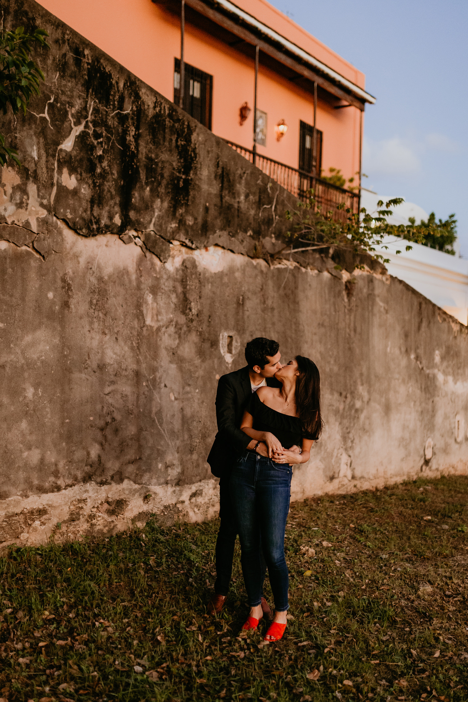man behind woman kissing each other in front of stone wall sunset light
