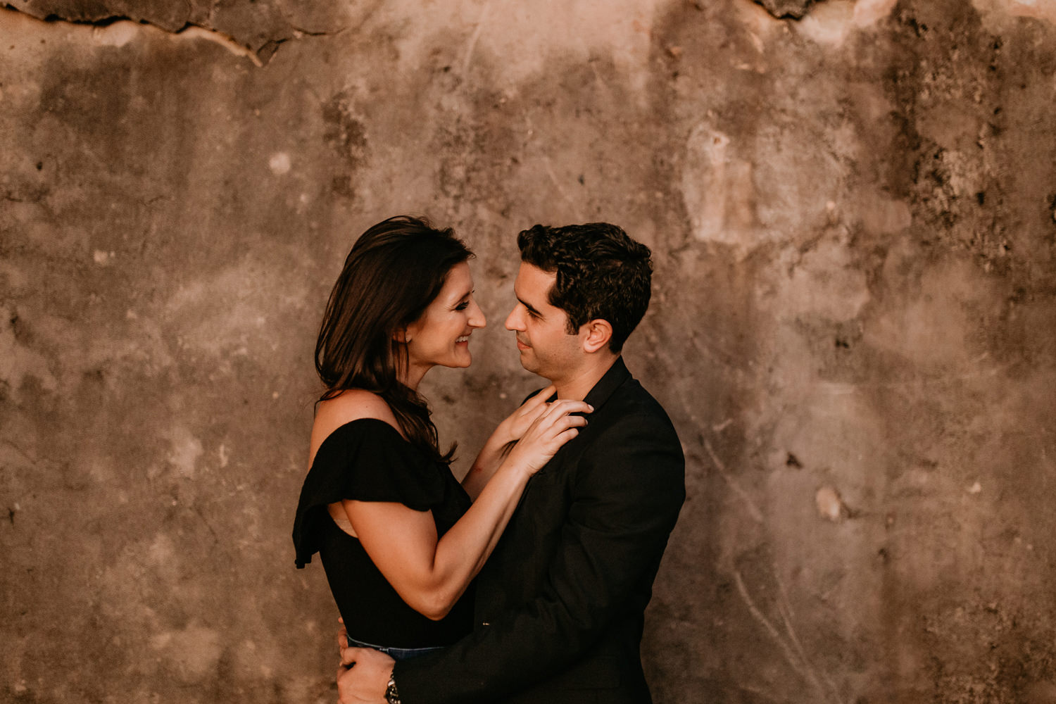couple facing each other smiling her hands on his chest in front of stone wall