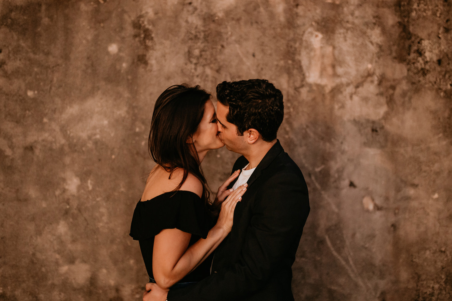 couple facing each other kissing her hands on his chest in front of stone wall