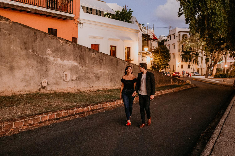 couple walking up San Juan street holding hands smiling with sunset light