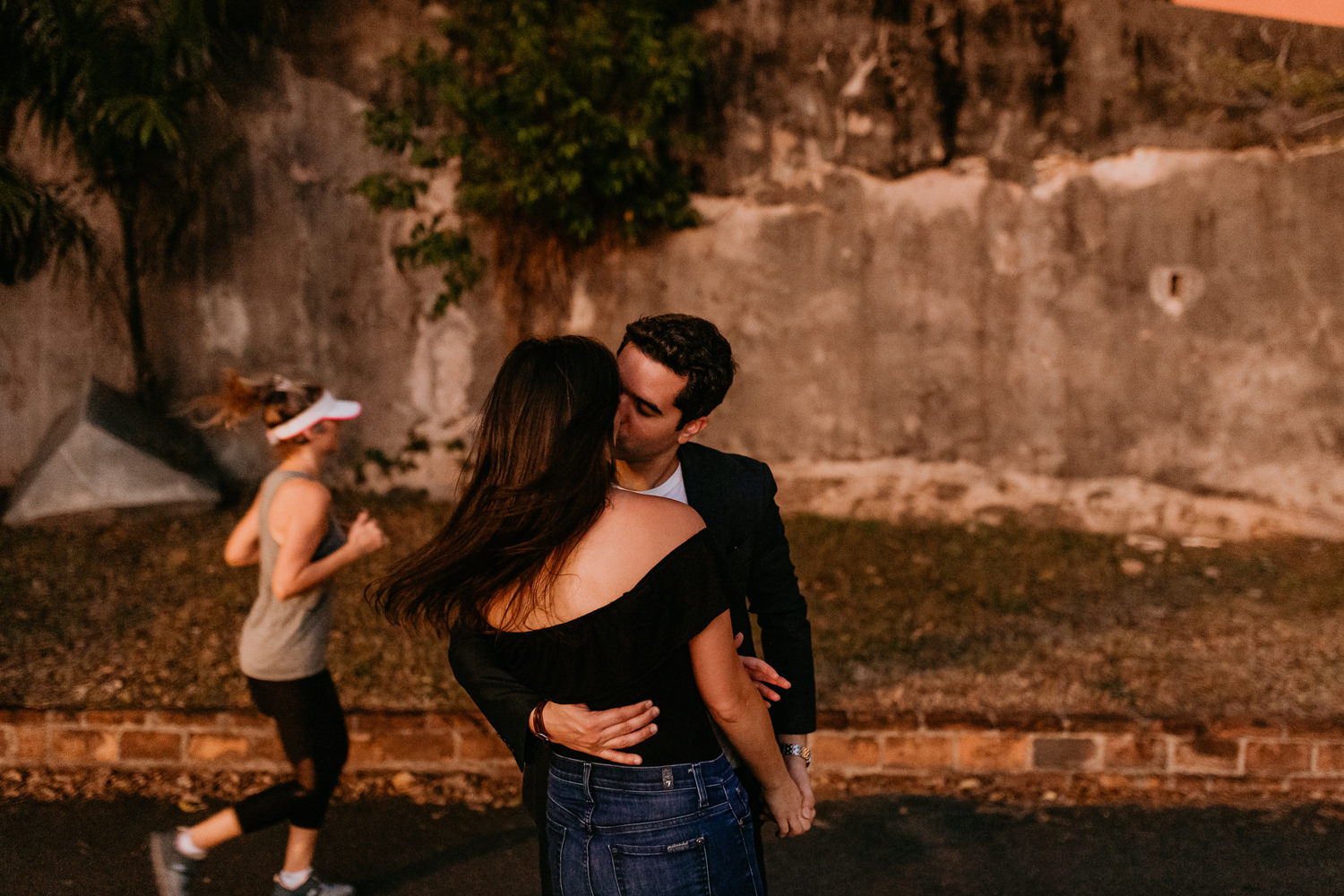 couple passionately kissing each other he has one arm around her waist